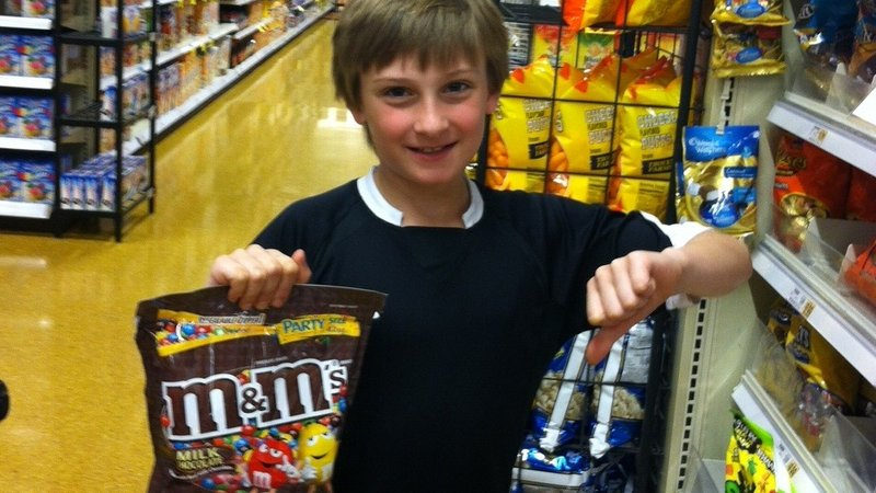 Boy holding a bag of candy and giving a thumbs-down sign.